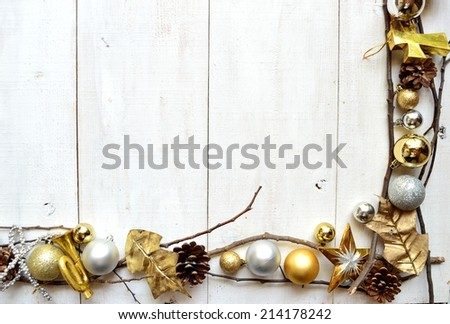 Gold and silver Christmas ornaments on white wooden background.