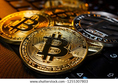 Gold and silver coins cryptocurrency lie on the laptop keyboard #1255307803