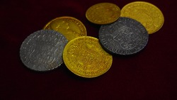 Gold and silver coins of the Spanish empire, Escudos y Reales. Shiny numismatic pieces on maroon background.