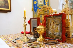 Gold and silver communion bowls, candles, icons and the Holy Gospel on the throne of the Orthodox Church. The concept of Orthodoxy.
