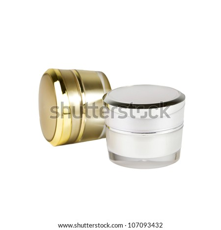 gold and silver container of cream on white background