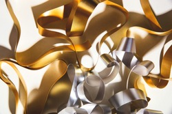 Gold and silver curl ribbon on white background in hard light with shadows.