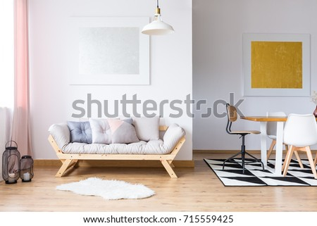 Gold and silver gallery in spacious room with pastel pillows on sofa and dining table on black and white carpet #715559425