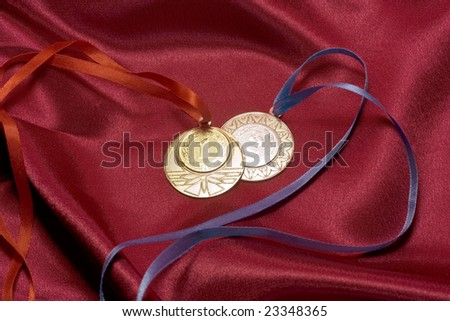 Gold and silver medals on red
