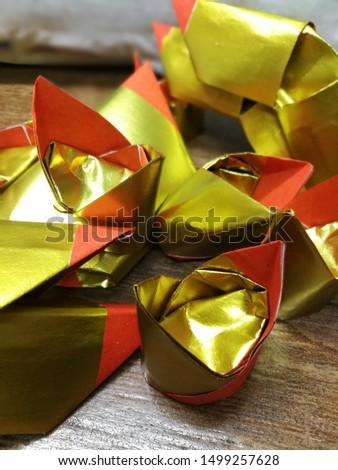 gold and silver paper that is folded into a gold shape before making offerings for ancestors