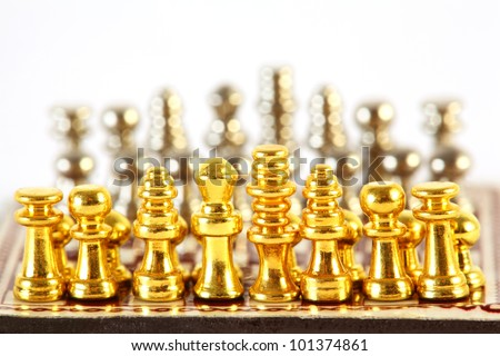 Gold and silver small chess stand on checkerboard; complete set