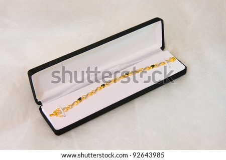 Gold and sterling silver bracelet in jewelry box adorned with sapphire and diamonds on white background