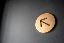 Gold arrow sign in circle shape frame  hanging against black wall for direction.