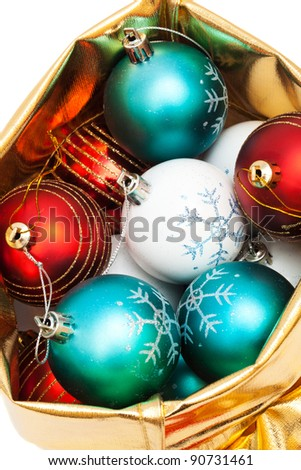 gold bag with Christmas balls on white background