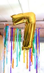 Gold balloon number 7. Child's birthdayparty decor in rural room interior