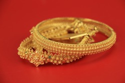 Gold bangle Isolated on red background.