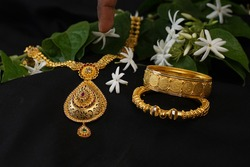 Gold Bangles And Traditional Gold Chain And Wild Jasmine