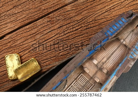 395126154de5 Gold bar beside the old plastic ancient ship model put on the hard wood  brown color