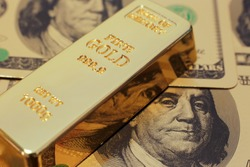 Gold bar on US dollar background. Conceptual image of gold trading, gold future, commodity trading, save heaven, currency backing and hedging
