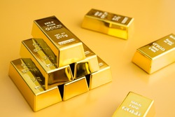 Gold bars or bullion stack on yellow background. Financial, global world economic or gold trading in commodity market concept. It performs well during global crises.