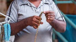 Gold beads in male hands, Puttaparthi, India. With selective focus