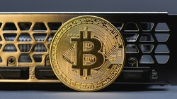 Gold Bitcoin coin on a  video Card on gray background,  close up. Crypto currency. Bitcoin mining concept