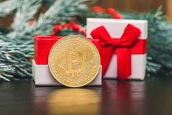 Gold bitcoin coin stands next to a gift box on the table against the background of a spruce branch with snow. Beautiful Christmas, new year background with bitcoin, a great gift. Digital currency.
