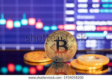 Gold Bitcoin crypto currency on background of chart diagram.
