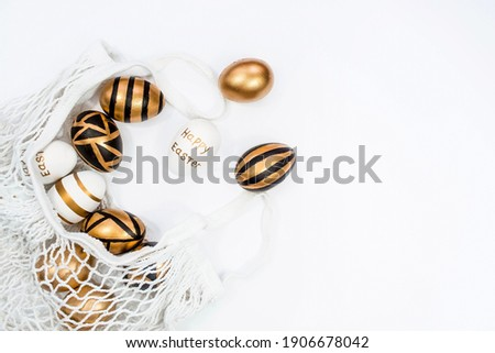 Gold, black, white Easter eggs in a string bag on a white background. Geometry. The minimal concept. Top view. Card with a copy of the place for the text.