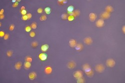 Gold bokeh stars on purple background. Yellow glitter backdrop. Golden texture. New year luxury snow. Copyspace. Shimmer confetti wallpaper. Dreamy shiny design detail