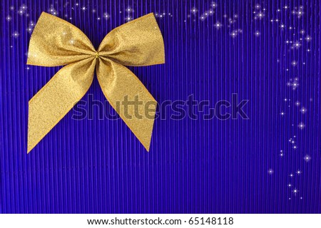 gold bow on blue background.	 - stock photo