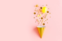 Gold box with confetti, balloons, streamers and decoration on a pink background. Colorful celebration, birthday background. Flat lay, top view