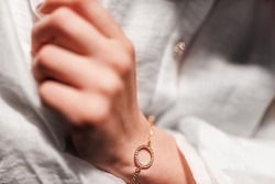 gold bracelet in the form of a ring with diamonds on a chain, girl's hand, sleeve of a white shirt, dark background.
