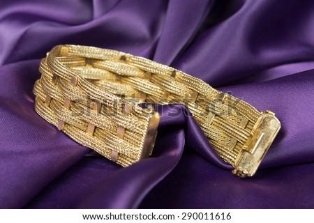 Gold bracelet isolated on purple satin background.