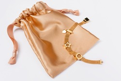 Gold bracelet on golden silk gift bag, jewelry flatlay on neutral background. Top view of fashion luxury woman accessories, jewelry and shopping concept. Trendy flat lay composition.