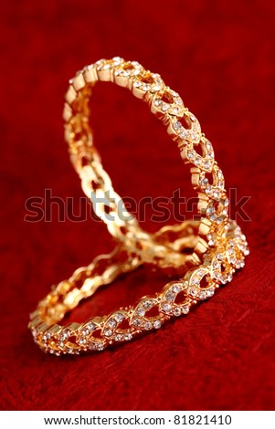 Gold bracelet on textured background. - stock photo
