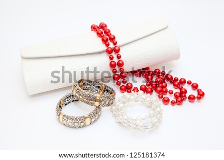 Gold bracelets red and white necklace with purse on white background