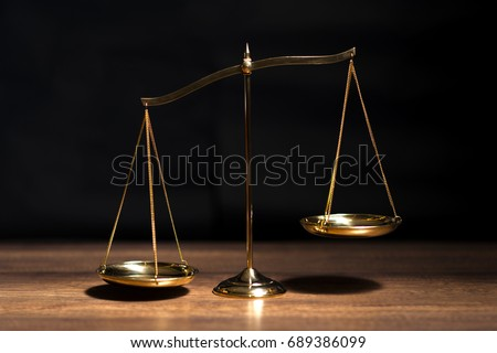 Gold brass balance scale,weight balance, imbalance scale on wooden desks with black background.