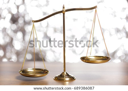 Gold brass balance scale,weight balance, imbalance scale on wooden desks with bokeh background.