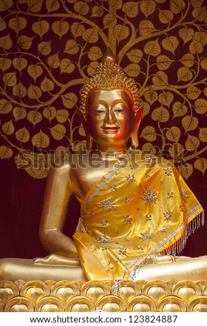 Gold Buddha figure set in front of a red and gold decorative background Thailand