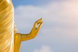 Gold buddha hand. Big buddha hand sculpture with blue sky in background. Buddha hand statue with sun light. Close up hand.