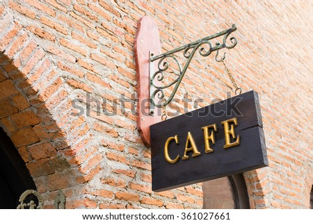 gold cafe sign above a brick...