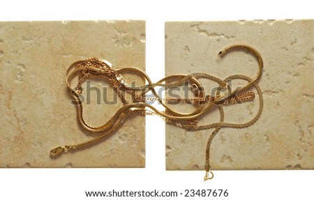 gold chainlets lie on the badly treated stone