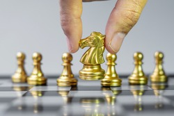 Gold Chess Knight figure Stand out from the crowd on Chessboard background. Strategy, leadership, business, teamwork, different, Unique and Human resource management concept