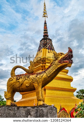Gold Chinthe Lion with View of Golden Theravada Buddhist Stupa and Blue Sky. Summer Day. (Huay Xai, Bokeo, Laos). #1208124364