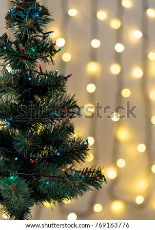 Gold Christmas background of de-focused lights garland with decorated tree #769163776