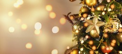 Gold Christmas background of de-focused lights with decorated tree