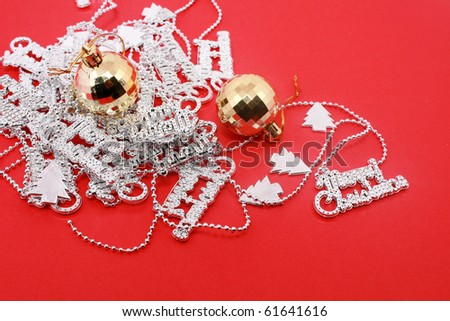 Gold Christmas ball and silver chritmas letter beads isolated on red