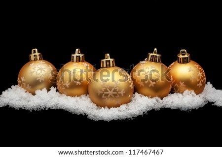 Gold christmas balls with snow isolated on black