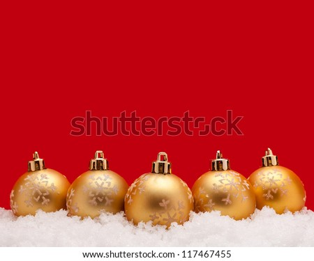 Gold christmas balls with snow isolated on red background