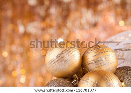 gold christmas baubles on background of defocused golden lights.