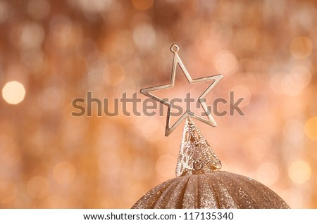 gold christmas baubles with star on top on background of defocused golden lights.