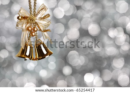 Gold Christmas bells on silver blurred background