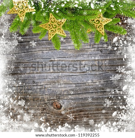 Gold christmas decoration baubles and pine on a snowbound wooden background