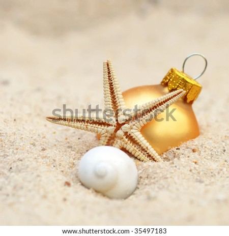 gold christmas ornament at the beach - for concept warm weather xmas - stock photo